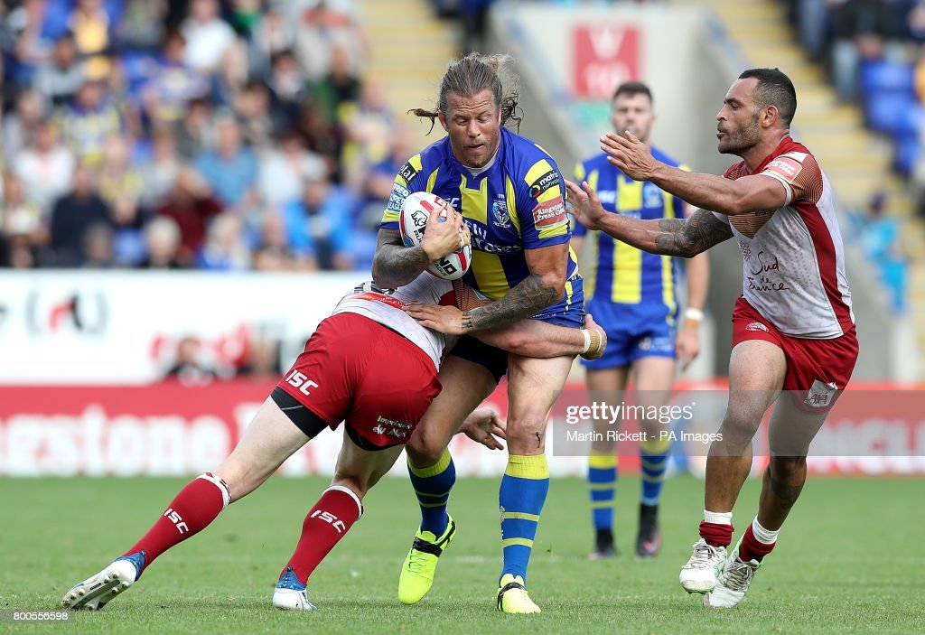 Warrington Wolves' Ashton Sims is tackled by Catalans Dragons' Remi Casty (left) and Paul Aiton (right), during the Betfred Super League match at the Halliwell Jones Stadium, Warrington.