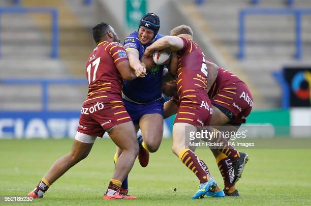 Warrington Wolves' Chris Hill is tackled by Huddersfield Giants Ukuma Ta'ai and Adam O'Brien and Sebastine Ikahihifo during the Betfred Super League...