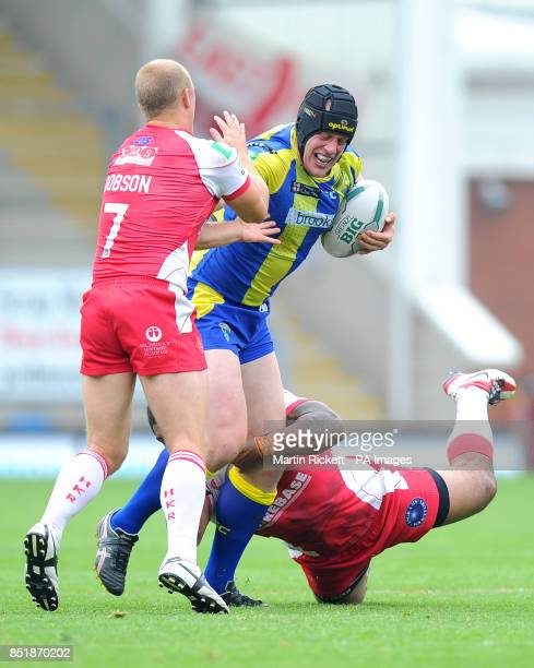 Warrington Wolves' Chris Hill is tackled by Hull Kingston Rovers' Michael Dobson and Michey Paea during the Super League match at the Halliwell Jones...