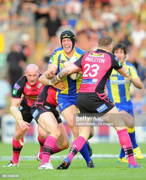 Warrington Wolves' Chris Hill is tackled by Leeds Rhinos Brad Singleton and Carl Ablett during the Super League match at the Halliwell Jones Stadium...