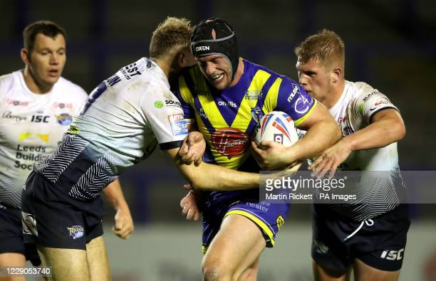 Warrington Wolves' Chris Hill is tackled by Leeds Rhinos' James Harrison and Tom Holroyd during the Betfred Super League match at the Halliwell Jones...