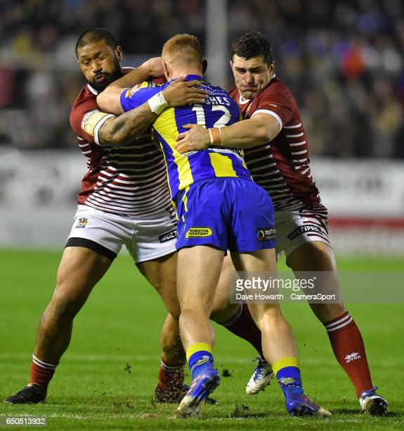 Warrington Wolves' Jack Hughes is tackled by Wigan Warriors' Ben Flower and FrankPaul Nu'uausala during the Betfred Super League Round 4 match...