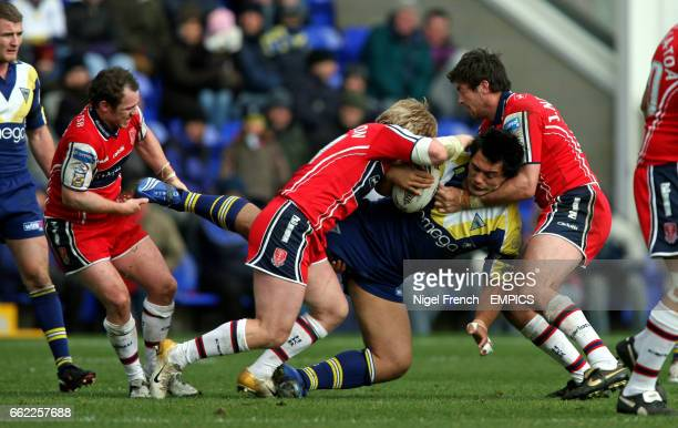 Warrington Wolves' Paul Rauhihi is put down by two Hull Kingston Rovers' tacklers