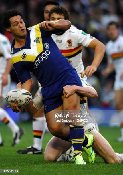 Warrington Wolves' Paul Rauhihi passes the ball as Bradford Bulls' Sam Burgess waits to pounce