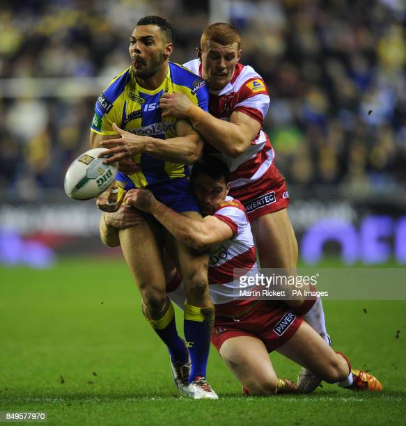 Warrington Wolves' Ryan Atkins is tackled by Wigan Warriors Jack Hughes and Matty Smith during the Super League match at the DW Stadium Wigan