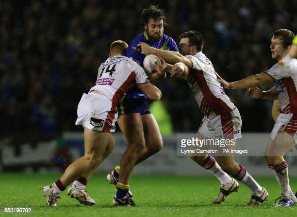 Warrington Wolves Trent Waterhouse is tackled by Wigan Warriors Jack Hughes Darrell Goulding and Logan Tomkins during the First Utility Super League...