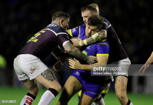 Warrington's Joe Philbin is tackled by Leeds Rhino's Brett Delaney and Adam Cuthbertson during the Betfred Super League match at the Halliwell Jones...