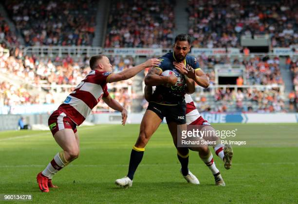 Warrington's Ryan Atkins is held up by Wigan Warriors Liam Farrell during the Betfred Super League Magic Weekend match at St James' Park Newcastle
