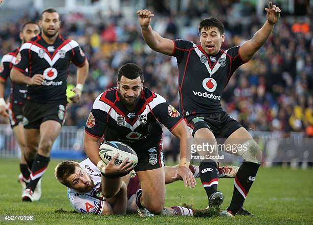 Warrior Ben Matulino is tackled by Kieran Foran with Ben Henry in support during the round 20 NRL match between the New Zealand Warriors and the...