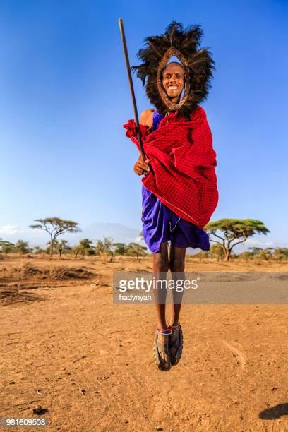 Warrior from Maasai tribe performing traditional jumping dance, Kenya, Africa