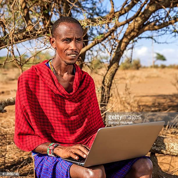 warrior from maasai tribe using laptop, kenya, africa - guerrier massai photos et images de collection