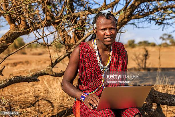 Warrior from Maasai tribe using laptop, Kenya, Africa