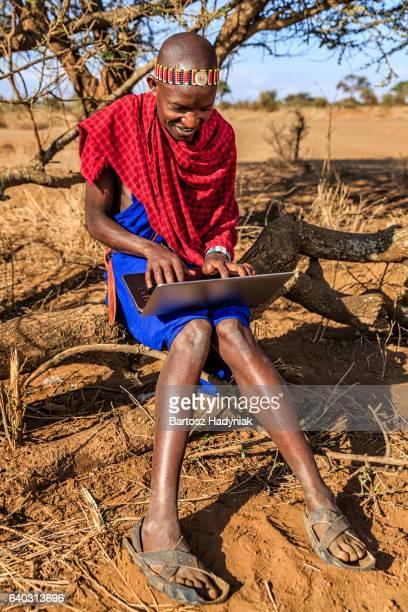 guerrier de maasai de la tribu se servant d'un ordinateur portable, kenya, afrique - guerrier massai photos et images de collection