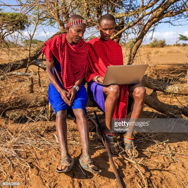 Warrior from Maasai tribe using laptop, Kenya, Africa
