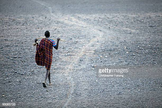 A warrior from the remote Turkana tribe in Northern Kenya walks across a dry riverbed as he tends to his herd of goats on November 9 2009 near Lodwar...