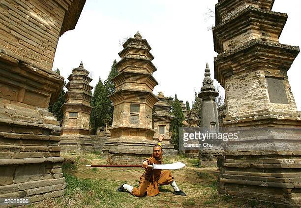 A warrior monk of Shaolin Temple displays his Kung Fu skills at the Pagoda Forest of the temple April 12 2005 in Dengfeng Henan Province China...