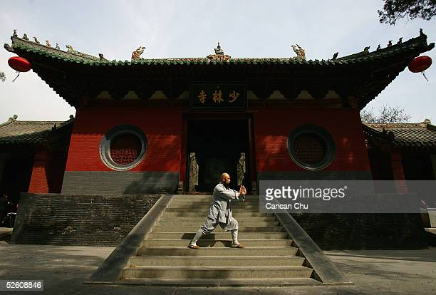 A warrior monk of Shaolin Temple displays his kung fu skills in front of the main gate of the temple April 7 2005 in Dengfeng Henan Province China...