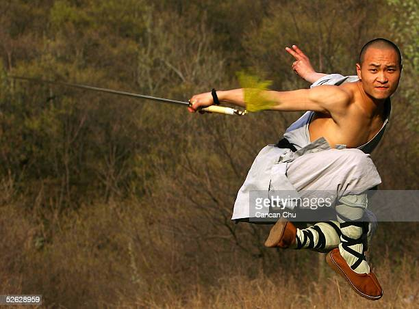 A warrior monk of the Shaolin Temple displays his Kung Fu skills at the Songshan Mountain near the temple April 12 2005 in Dengfeng Henan Province...