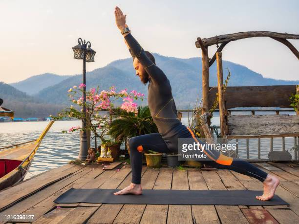 warrior pose on the lake. morning outdoors mens yoga - mujeres fotos stock pictures, royalty-free photos & images