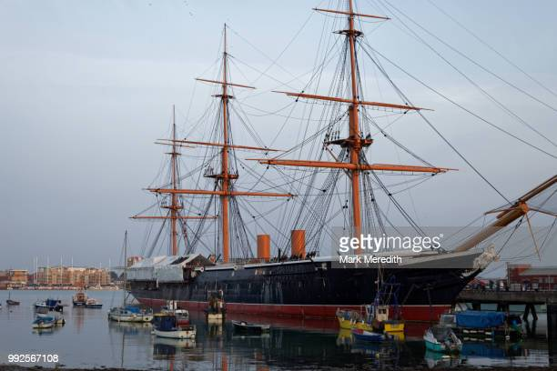 hms warrior, the first iron clad warship, on the hard in old portsmouth, hampshire, england - warship stock pictures, royalty-free photos & images