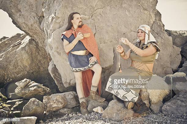 Warrior with a cup and a woman spinning next to him Illyrian civilisation mid3rd century BC Historical reenactment