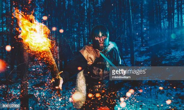 Warrior with flaming torch walks through forest at nigth ready to attack