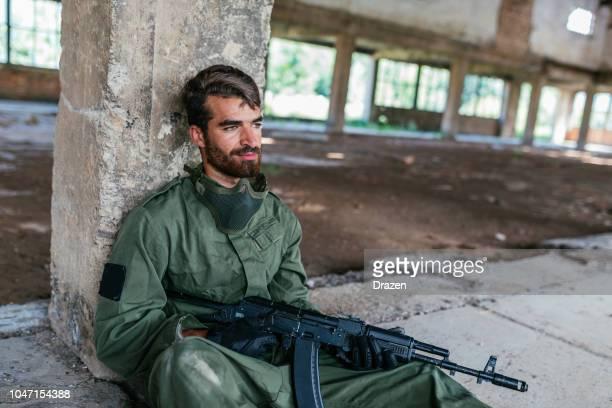 Warrior with gun resting after battle