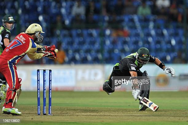 Warriors batsman Ashwell Prince completes a run while RCB wicket keeper AB de Villiers collects the ball during the Champions League Twenty20 League...