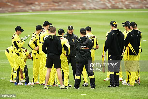 Warriors coach Justin Langer speaks to his players before the resumption of play after a long rain delay the Matador BBQs One Day Cup match between...