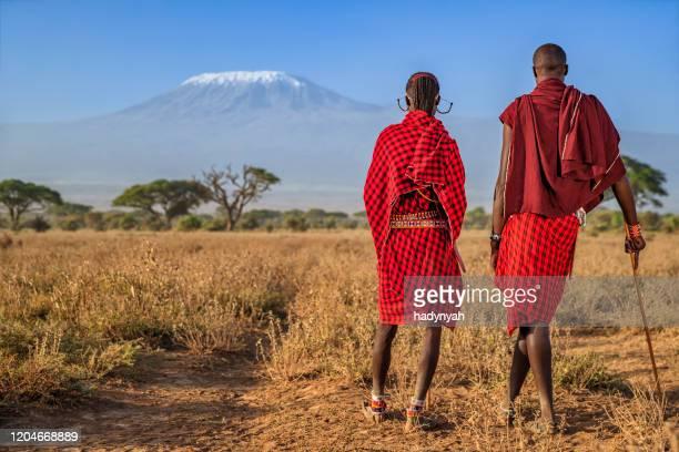 guerreros de la tribu maasai mirando al monte kilimanjaro, kenia, africa - kenia fotografías e imágenes de stock