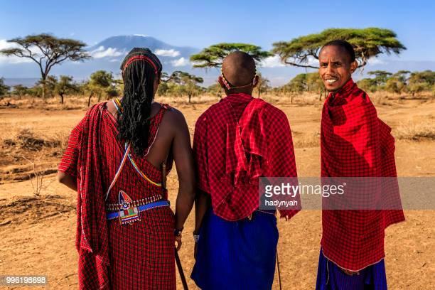 Warriors from Maasai tribe looking at Mount Kilimanjaro, Kenya, Africa