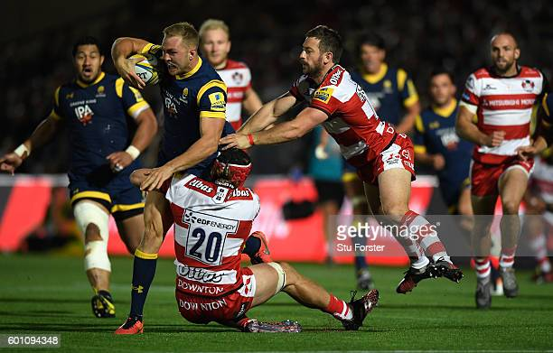 Warriors player Perry Humphreys breaks the tackle of Jacob Rowan and Greig Laidlaw of Gloucester during the Aviva Premiership match between Worcester...
