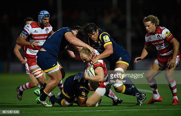 Warriors players Darren Barry and Donncha O' Callaghan converge on Matt Kvesic of Gloucester during the Aviva Premiership match between Worcester...