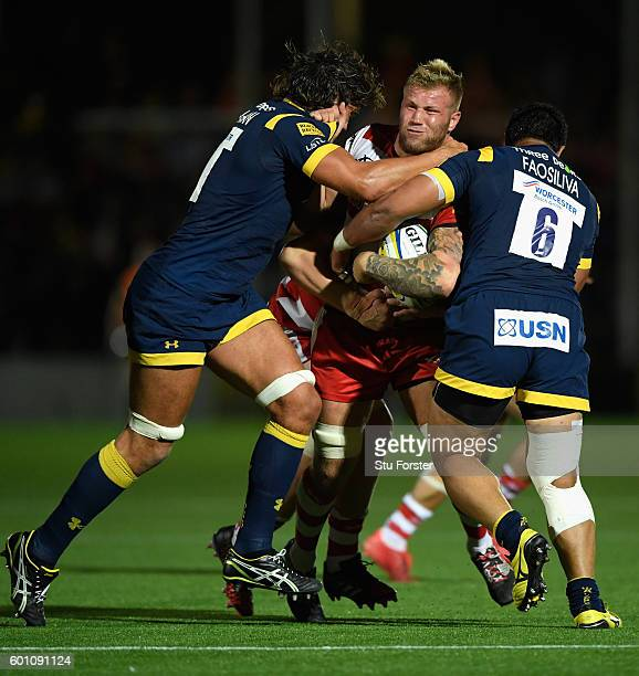 Warriors players Donncha O' Callaghan and Alafoti Faosiliva combine to tackle Ross Moriarty of Gloucester during the Aviva Premiership match between...