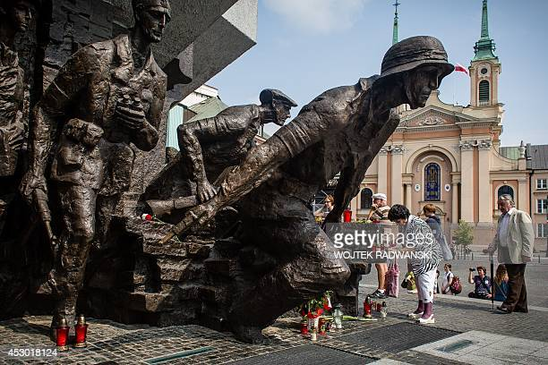 Warsaw citizens pay tribute in front of a monument to the Poles who fought Nazi German occupation troops in 1944 during ceremonies marking the 70th...