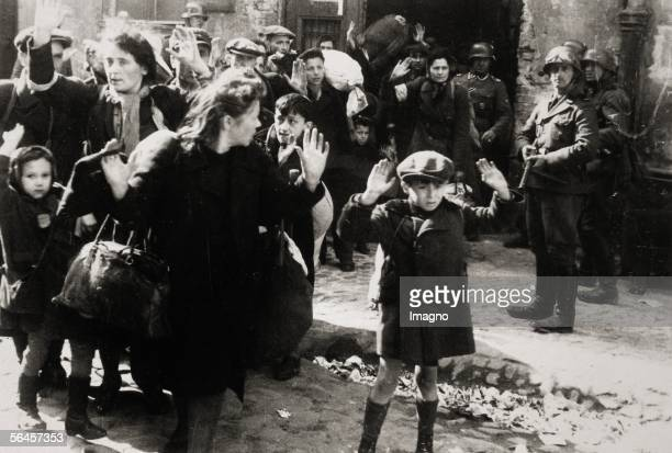Warsaw ghetto insurgence April/May 1943 Little boy with raised hands women and other children are leaving a house which was captured by the German...