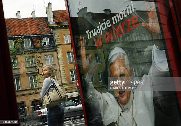 A Polish woman waits next to a poster announcing the visit of Pope Benedict XVI at a bus stop in central Warsaw 24 May 2006 Poland has been preparing...