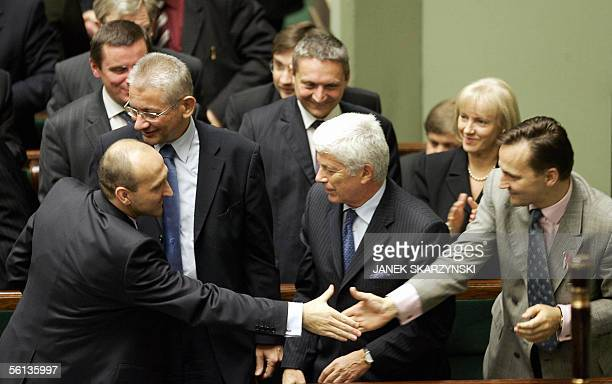 Conservative Polish Prime Minister Kazimierz Marcinkiewicz shakes hands with Defence Minister Radoslaw Sikorski in the presence of other members of...