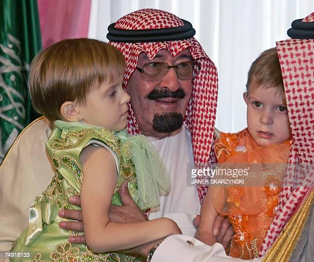 King of Saudi Arabia Abdullah bin Abdulaziz Al Saud holds Olga one of Polish Siamese twins Olga and Daria Kolacz who came with their mother Wieslawa...