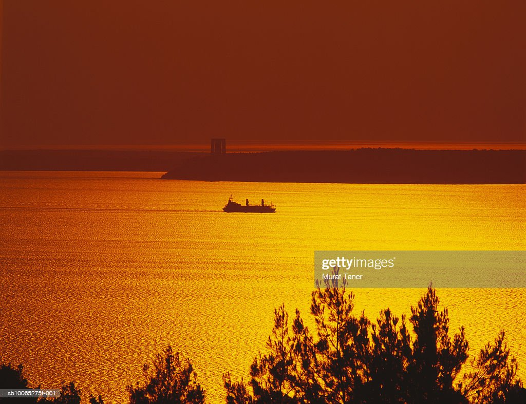 Warship in sea and Turkish War Monument in background at sunset : Foto stock