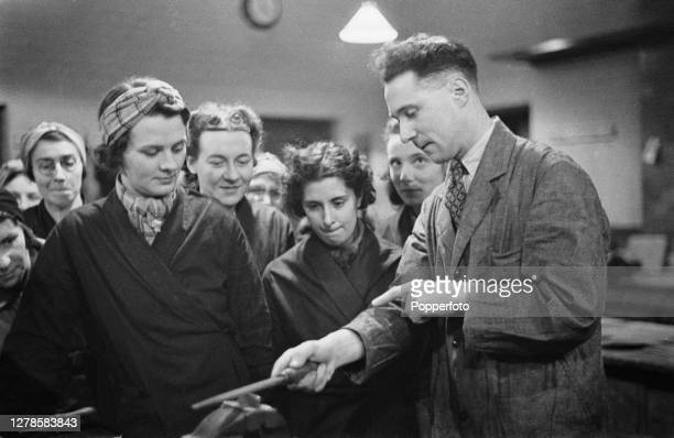 Wartime munitions worker Mrs Petts and her fellow female coworkers receive instructions on filing metal from an instructor in a factory workshop...