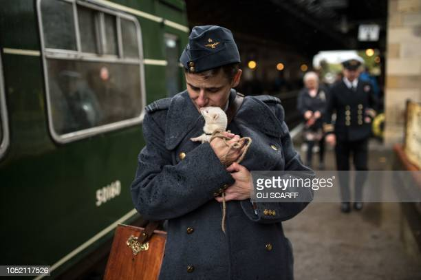 TOPSHOT A wartime reenactor cuddles a ferret as they prepare to board a train during a reenactmentthemed weekend the annual 'Railway in Wartime'...