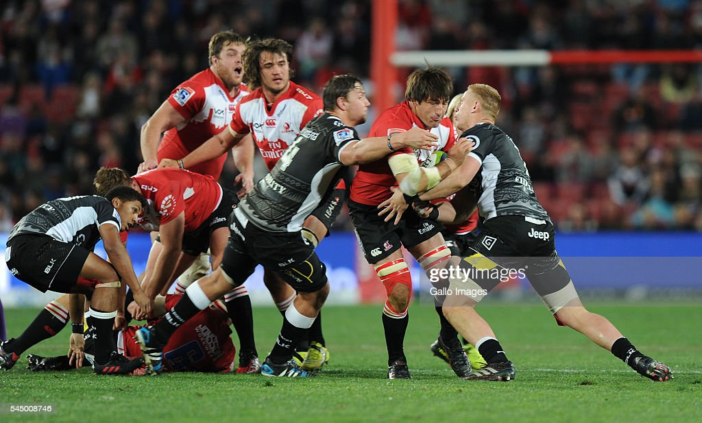 Warwick Tecklenburg of Lions is tackled by Etienne Oosthuizen and Jean-Luc de Preez of Sharks during the Super Rugby match between Emirates Lions and Cell C Sharks at Emirates Airline Park on July 02, 2016 in Johannesburg, South Africa.