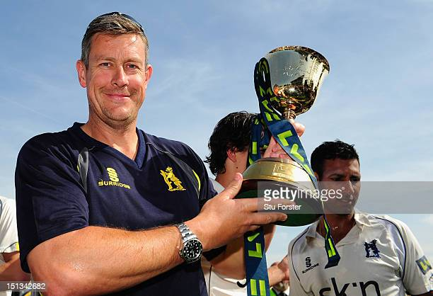 Warwickshire director of cricket Ashley Giles holds the trophy after winning the LV County Championship Division One title after day three of the LV...