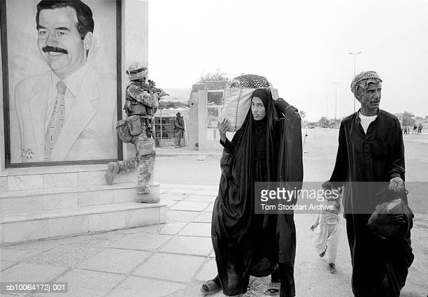 A wary Iraqi family pass a British Royal Marine Commando near a mural of Saddam Hussein on the day Basrah was liberated