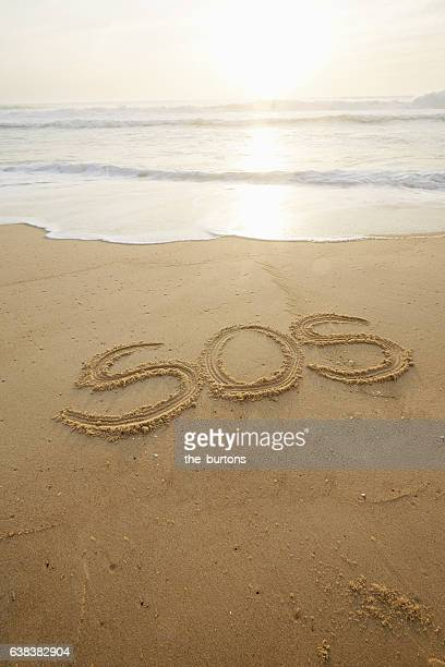sos was written in the sand - sos einzelwort stock-fotos und bilder