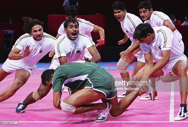 Waseem Sajjad of Pakistan is taken down by the team from India during the Men's Kabaddi Round Robin match at the 15th Asian Games Doha 2006 at Aspire...