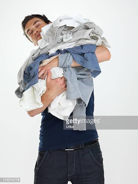 Washday-junger Mann schaut Ihre Wäsche