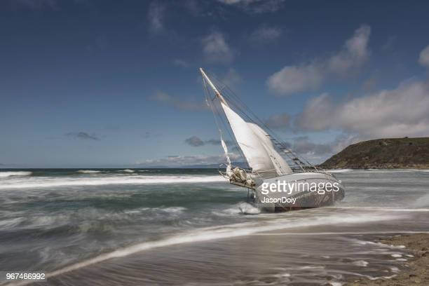 washed ashore sailboat on beach - ship wreck stock pictures, royalty-free photos & images