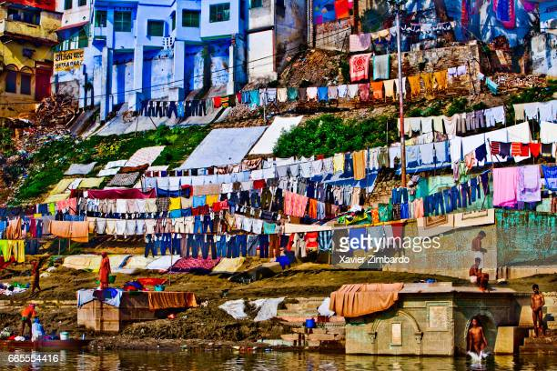 Washermen and women washing laundry with their hands and drying clothes at the Dhobi Ghat while some pilgrims are bathing on the banks of River...